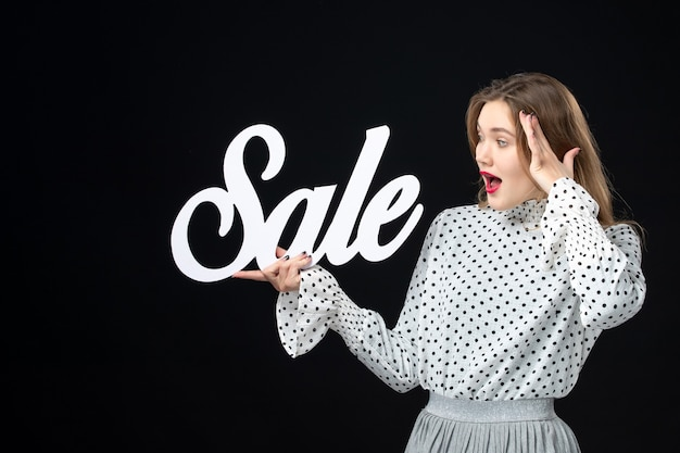 Front view young pretty female holding sale writing on a black wall shopping beauty fashion emotion color model photo