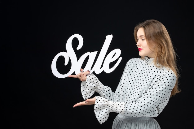 Front view young pretty female holding sale writing on black wall shopping beauty fashion emotion color model photo