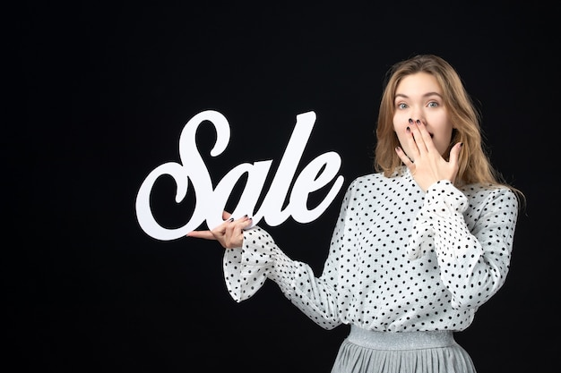 Front view young pretty female holding sale writing on the black wall shopping beauty fashion emotion color model photo