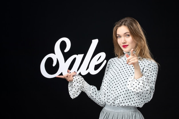 Front view young pretty female holding sale writing on black wall shopping beauty fashion emotion color model photos