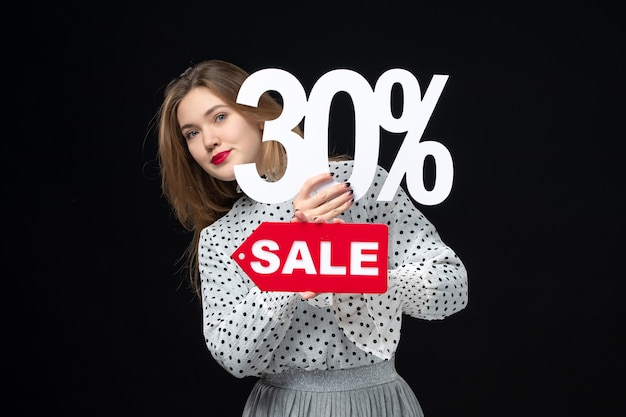 Vista frontale giovane bella donna che tiene la scrittura in vendita e sul muro nero modello donna emozione shopping colori moda