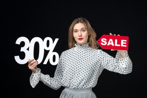 Vista frontale giovane bella donna che tiene la scrittura in vendita e sul muro nero modello donna shopping bellezza moda emozione