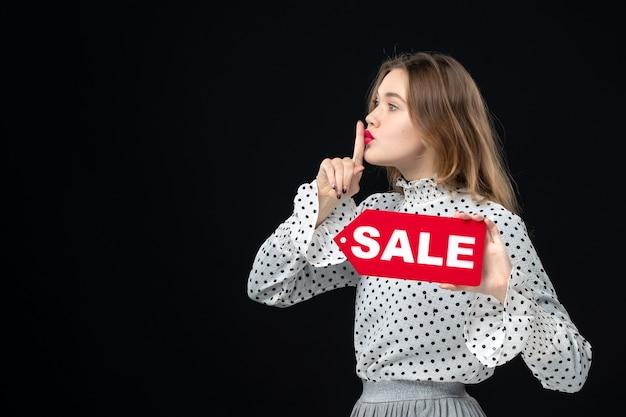 正面図若いきれいな女性が販売を保持している黒い壁の色のショッピングファッション写真女性の感情赤
