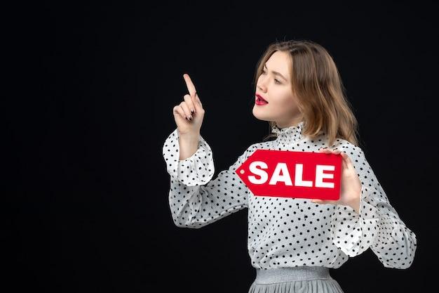 正面図若いきれいな女性が販売を保持している黒い壁の色のショッピングファッション写真女性赤に書き込みます