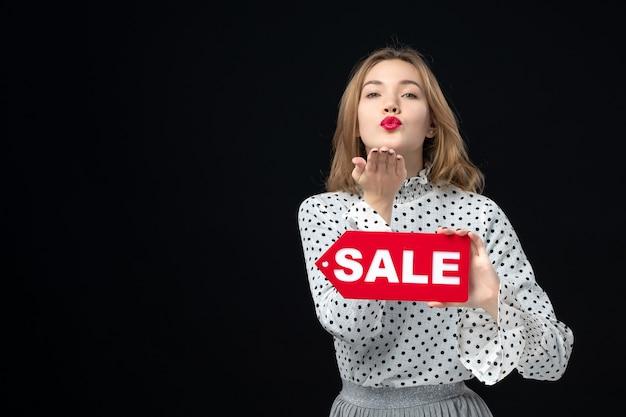 正面図若いきれいな女性が販売を保持している黒い壁の色のショッピング女性の感情の赤いファッションに書き込みます
