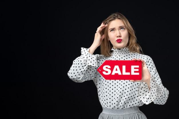 正面図若いきれいな女性の販売を保持している黒い壁の感情の赤い写真ファッション女性の色に書き込みます