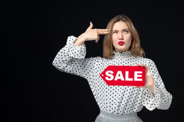 正面図若いきれいな女性の販売を保持している黒い壁の感情赤いショッピング写真ファッション女性の色に書き込みます
