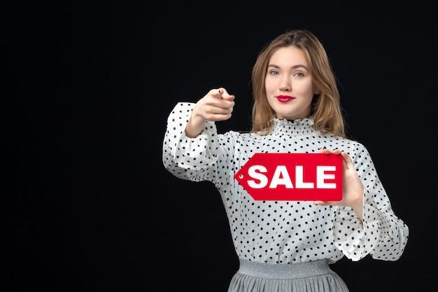 正面図若いきれいな女性の販売を保持している黒い壁の感情に書き込み赤いショッピング写真ファッション女性の色