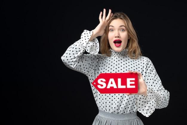 正面図若いきれいな女性が販売を保持している黒い壁モデル美容感情ショッピングファッション色赤