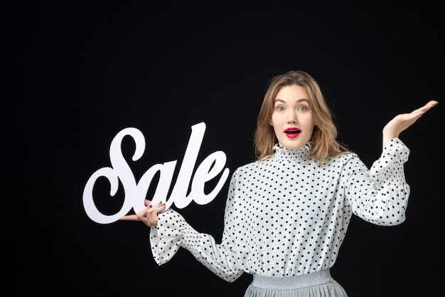 전면 보기 검은 벽 모델 쇼핑 아름다움 감정 색상에 판매 쓰기를 들고 젊은 예쁜 여성