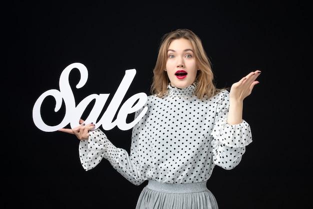 正面図若いきれいな女性が黒い壁に販売を書いているショッピング美容感情カラーモデル写真ファッション