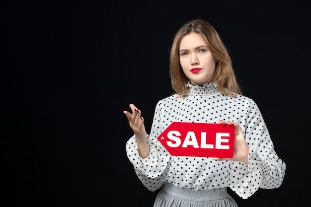 Вид спереди молодая симпатичная женщина, держащая распродажу, писать на черной поверхности, модель красоты, эмоции, шоппинг, мода, женщина, цвет