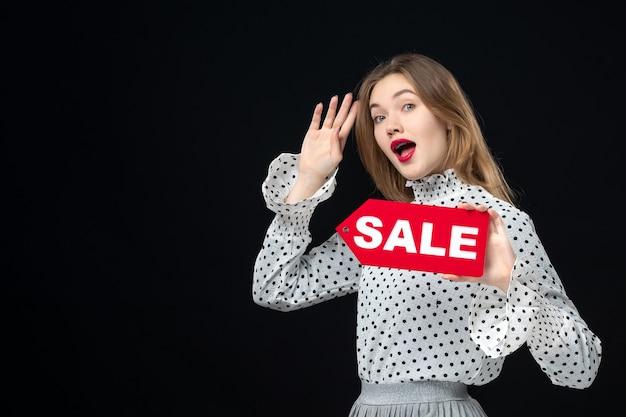 Вид спереди молодая симпатичная женщина, держащая распродажу, написание на черной стене, цвет покупок, мода, фото, женщина, эмоция, красный