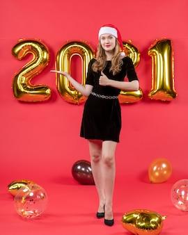 赤のサイン風船を親指を作る黒のドレスで若いきれいな女性の正面図