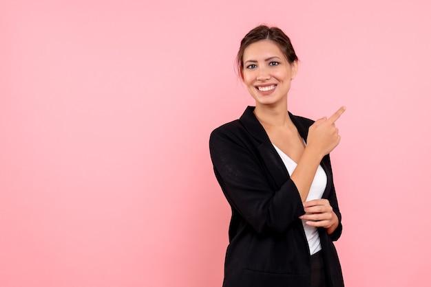 Вид спереди молодая красивая женщина в темной куртке на розовом фоне