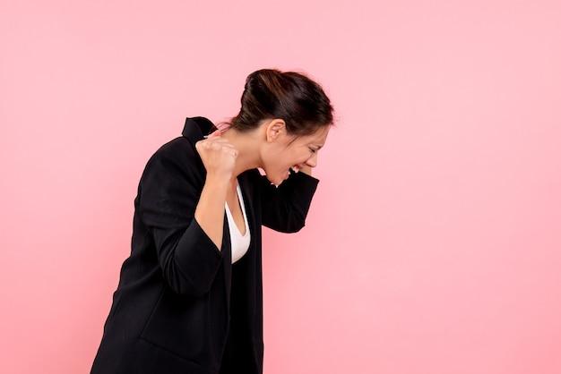 ピンクの背景に暗いジャケットを着た若いきれいな女性の正面図