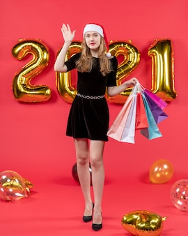 Front view young pretty lady in black dress hailing someone holding shopping bags balloons on red
