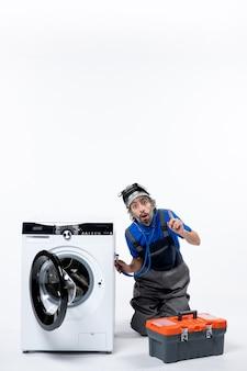 Vista frontale del giovane riparatore che mette lo stetoscopio sulla lavatrice seduto vicino alla lavatrice sul muro bianco