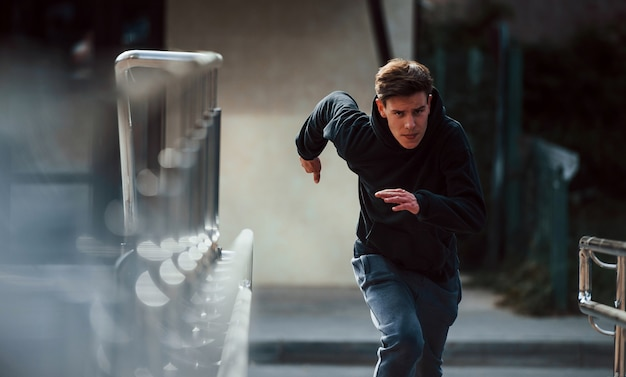 Front view of young runner in black clothes that is in the city.