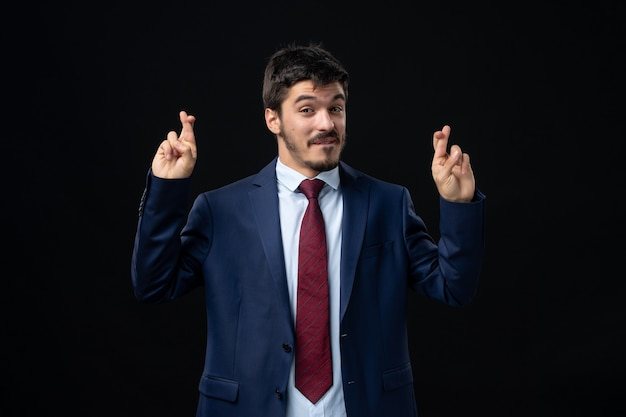 Front view of young and satisfied bearded man crossing his fingers on isolated dark wall