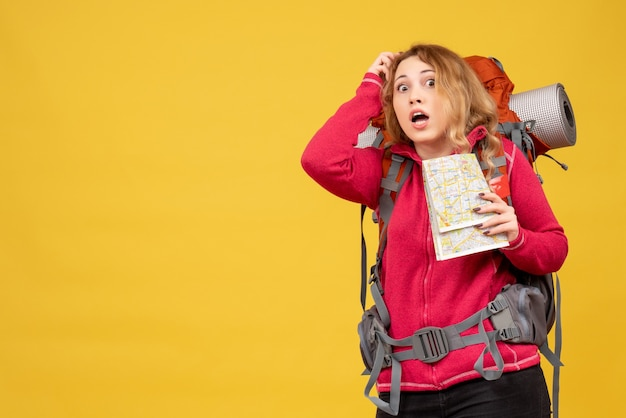Vista frontale della giovane ragazza in viaggio spaventata in mascherina medica raccogliendo i suoi bagagli e tenendo la mappa