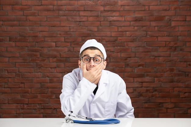 Вид спереди молодой потрясенный доктор в белом медицинском костюме на стене из коричневого кирпича