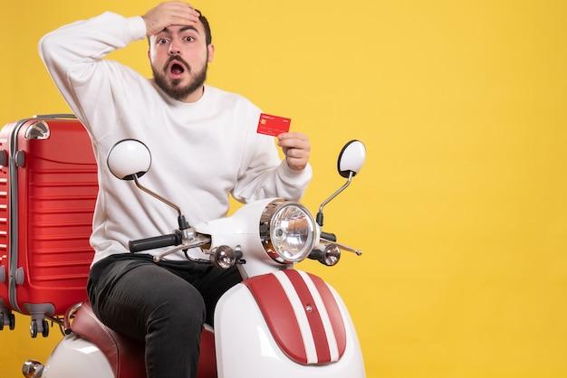Vista frontale di un giovane uomo in viaggio scioccato seduto su una moto con la valigia sopra che tiene una carta di credito su sfondo giallo isolato