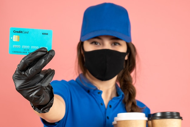 Vista frontale della giovane ragazza sorridente del corriere che indossa guanti con maschera medica in piedi accanto alla moto con in mano un caffè con carta di credito su sfondo color pesca pastello