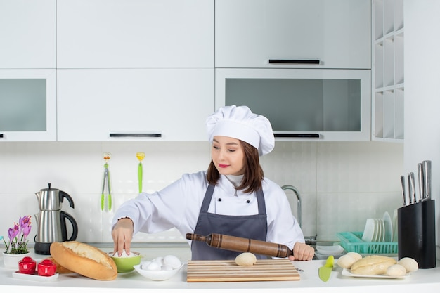 Front view of young smiling female chef in uniform standing behind table preparing pastry in the white kitchen