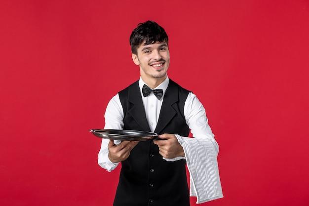 Vista frontale di un giovane cameriere maschio sorridente in uniforme con papillon sul collo che tiene vassoio e asciugamano sulla parete rossa