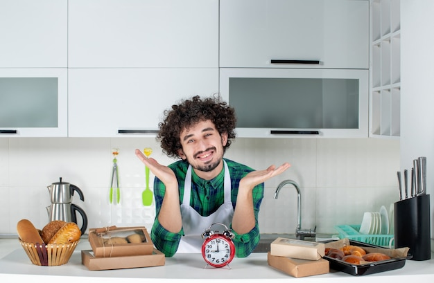 Vista frontale del giovane uomo sorridente in piedi dietro l'orologio da tavolo vari pasticcini nella cucina bianca