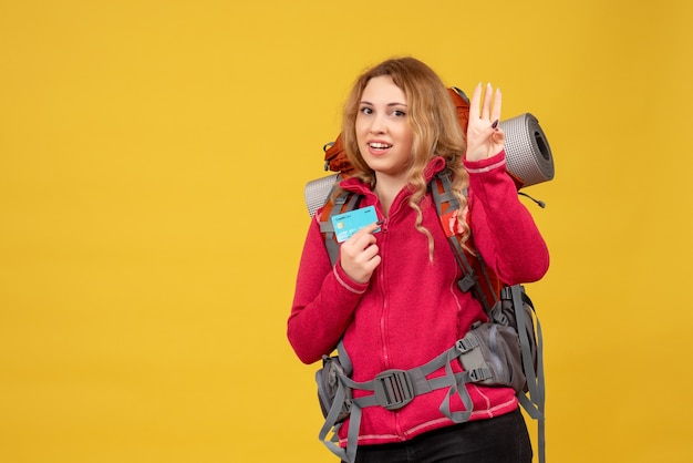 Vista frontale della giovane ragazza sorridente in viaggio nella mascherina medica raccogliendo i suoi bagagli e mostrando tre