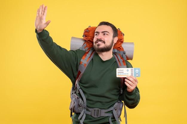 Vista frontale del giovane ragazzo in viaggio sorridente con lo zaino e che mostra il biglietto su sfondo giallo