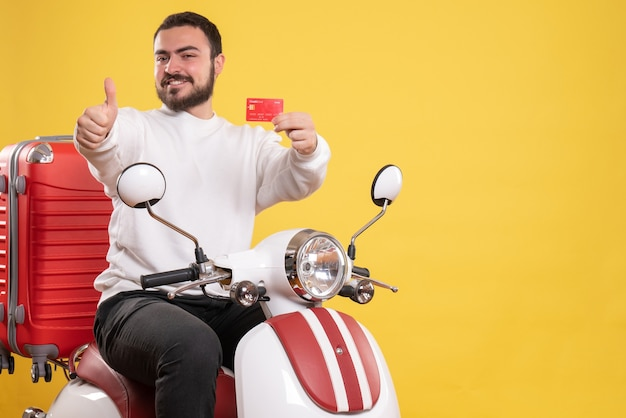 Front view of young smiling travelling man sitting on motorcycle with suitcase on it holding bank card making ok gesture on isolated yellow background