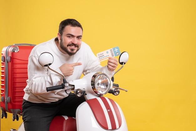 Vista frontale di un giovane viaggiatore sorridente seduto su una moto con la valigia sopra che tiene il biglietto su sfondo giallo isolato