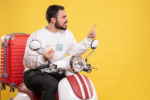 Vista frontale di un giovane uomo in viaggio sorridente seduto su una moto con la valigia sopra che tiene il biglietto rivolto verso l'alto su sfondo giallo isolato