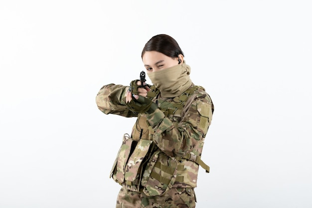 Front view of young soldier in camouflage aiming gun on a white wall