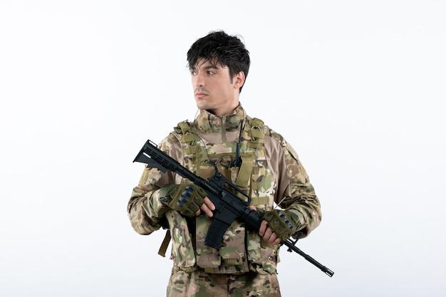 Vista frontale del giovane soldato in uniforme militare con la parete bianca della mitragliatrice
