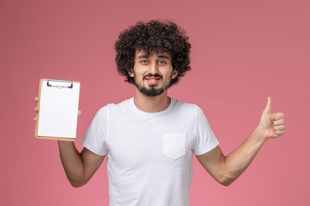 Giovane studente di vista frontale che dà i pollici fino al taccuino bianco su fondo rosa isolato