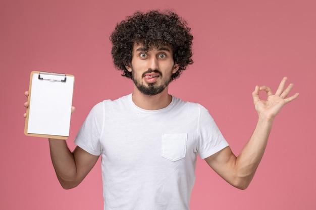 ノートブックを保持し、孤立したピンクの背景でokジェスチャーをしている正面図若い学生
