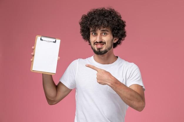 白いtシャツで彼の白いノートを示す正面図の若い学生