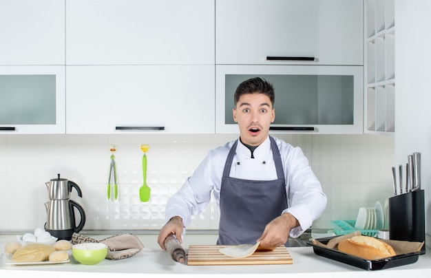 Front view of young surprised commis chef in uniform wearing holder and preparing pastry in the white kitchen