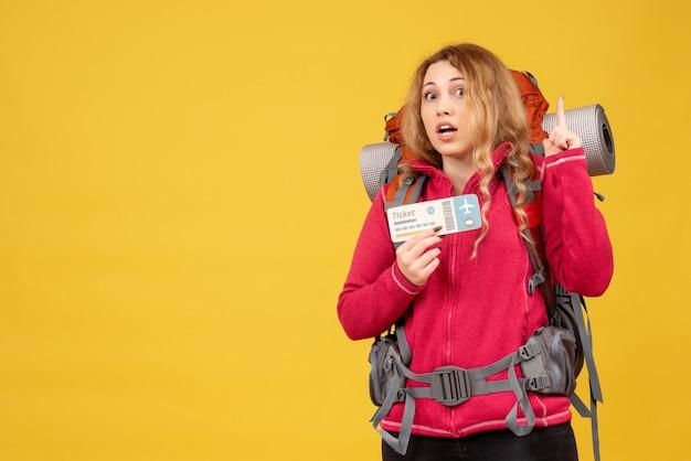Vista frontale della giovane ragazza di viaggio sorpresa in mascherina medica che tiene biglietto e rivolto verso l'alto