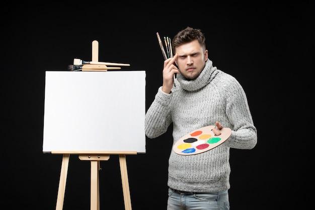 Vista frontale del giovane pittore maschio sconcertato di talento che tiene la pittura a olio di colore della miscela sulla tavolozza e sui pennelli sul nero