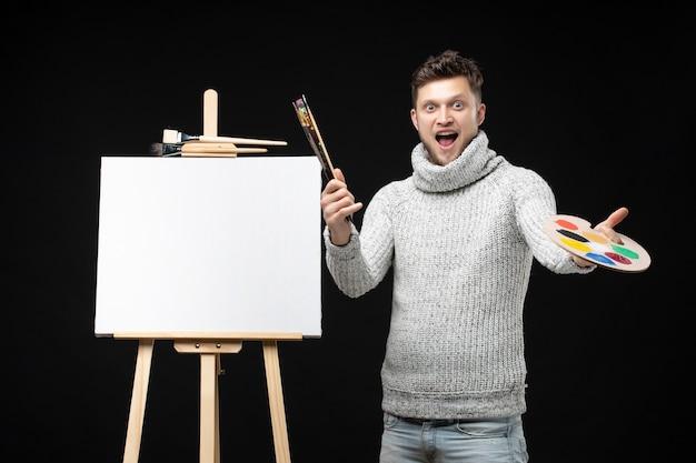 Vista frontale del giovane pittore maschio emotivo divertente e di talento che mostra la pittura a olio di colore della miscela sulla tavolozza sul nero