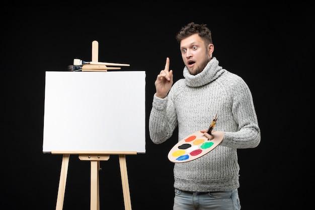 Vista frontale del giovane pittore maschio sorpreso di talento che pensa sul nero