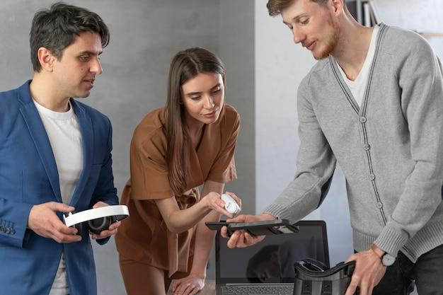 Vista frontale del giovane team di professionisti che lavorano con laptop e cuffie