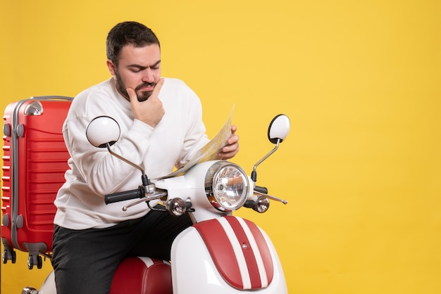 Front view of young thinking man sitting on motorcycle with suitcase on it holding map on isolated yellow background