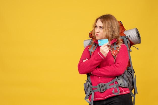 Vista frontale della giovane ragazza di viaggio di pensiero nella mascherina medica che raccoglie i suoi bagagli che tengono la carta di credito