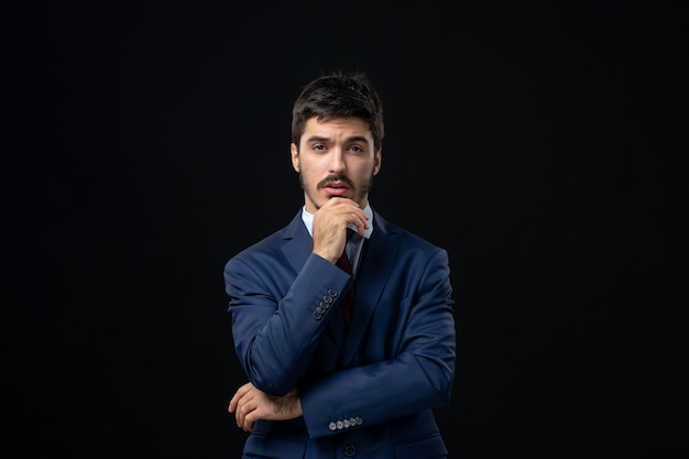 Front view of young thoughtful bearded man posing on isolated dark wall